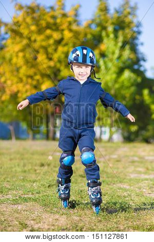 Cute little boy posing on roller skates outdoors