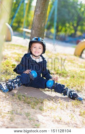 Smiling skater boy in helmet sitting near the tree