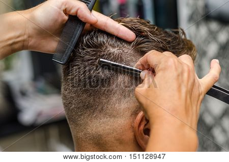 Hairdresser Cutting Man's Hair With Toothed Razor