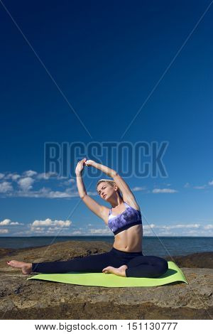 caucasian woman stretching at the sea shore during summer training