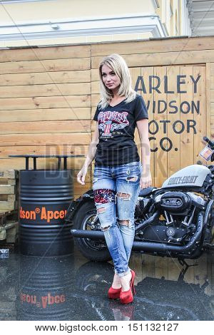 """St. Petersburg, Russia - 12 August, Girl posing on a background of a motorcycle,12 August, 2016. Beauty contest """"Miss St.Petersburg Harley Days 2016"""" at the annual festival Harley Davidson in St. Petersburg."""