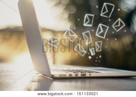 Side view of laptop with e-mail icons. Communication concept