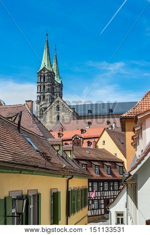 View of a typical old narrow street in the historical center of UNESCO world heritage town Bamberg Bavaria Germany. Bamberg Cathedral in the background.