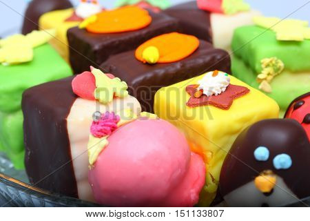 Various colorful marzipan cakes on glass plate
