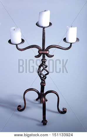 Single tall iron candelabra with three candles