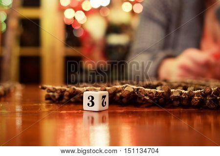 Dice on old wood table while family plays a game