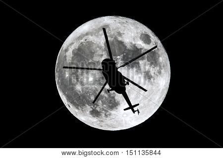 The full Moon is seen isolated on a black background. High contrast high resolution image taken with a full frame dslr camera. A silhouette of a helicopter passing in front of the moon.