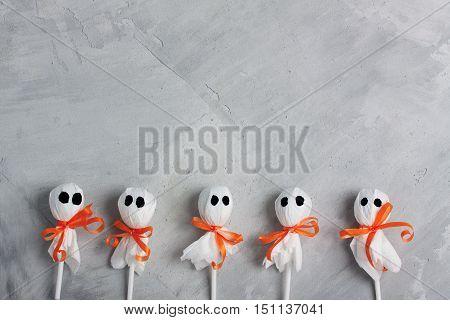 Halloween lollipop ghosts on gray concrete background horizontal orientation