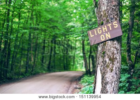 Lights On Sign in a small road in upstate New York. Surrounded by trees and forest