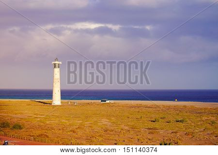 View on a light house the sea and a sand beach with aprotected natual park in Morro Jable the south part of the Canary Island Fuerteventura Spain.