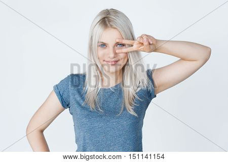Natural makeup. White Hairstyle. Studio portrait of smiling blond girl over grey background showing peace sign. Two fingers symbol
