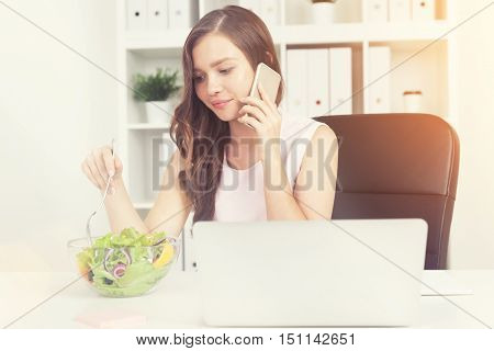 Woman in office eating salad at working place. Laptop at table. She is on her phone. Bookcase with binders plants and coffee at background. Sunny. Concept of lunch at work. Toned image