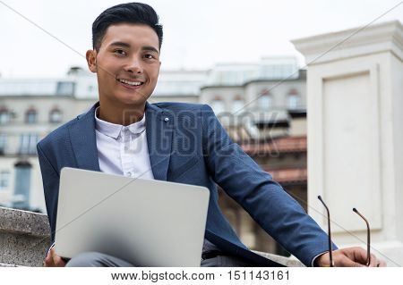 Smiling Asian man in dark blue suit sitting in the street and checking his social media during lunch break in the office. Concept of living in digital world