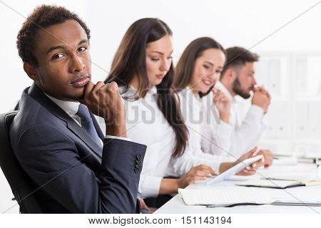 Pensive African American businessman is looking at his colleague off camera and imagining he is doing something interesting. Concept of business routine