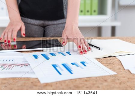 Close up of girls hands touching tablet screen and diagram on sheet of paper. Concept of statistician's work