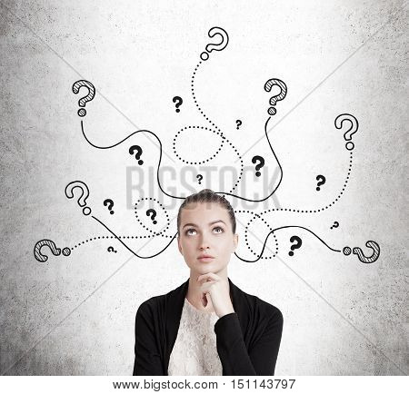 Portrait of woman in black cardigan standing near concrete wall with question mark sketches on it. Concept of pondering and analyzing the facts