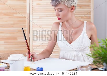 Serious woman painter is creating her masterpiece in office with wooden screen and a potted plant. Concept of design