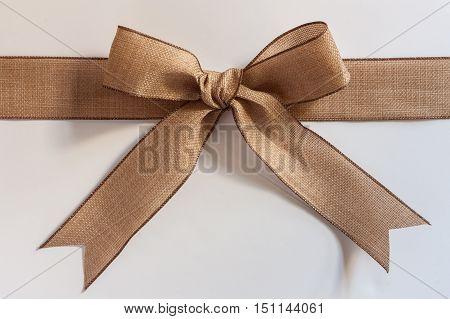 Beige linen ribbon bow isolated on white background