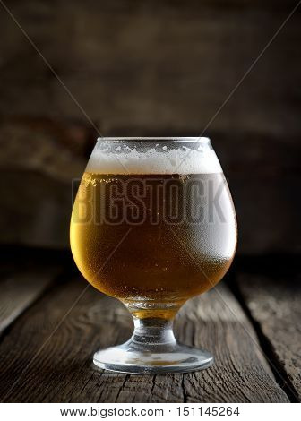 cold frothy beer in a glass on a dark wooden background