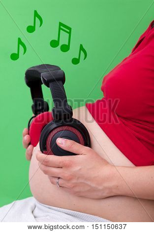 Pregnant woman with headphones on her stomach