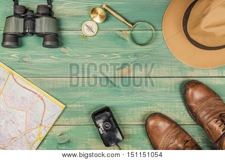 Tourism concept. Magnifying glass compass city map binoculars brown shoes fedora hat and old film camera on green wooden background