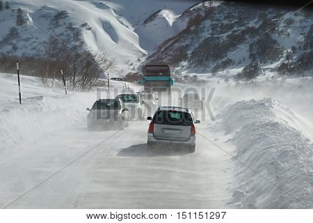 Cars in blizzard on an alpine road