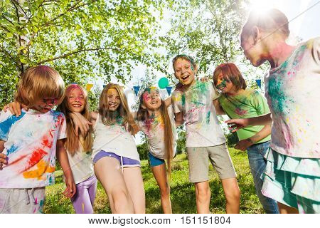 Big group of kids, smeared with colored powder, dancing and having fun during the festival of colors and spring