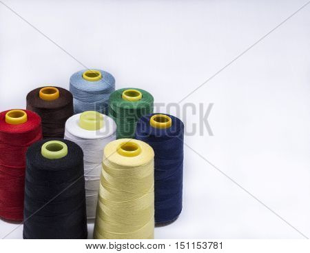 Colorful assortment of vivid colors of cotton spools on cones for use in the knitwear and garment industry viewed high angle