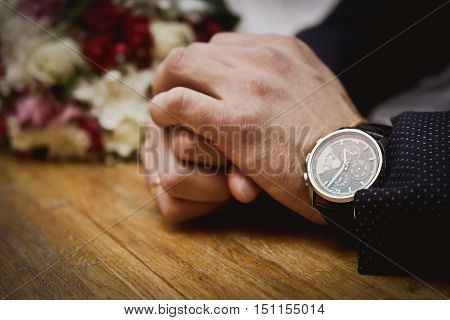 hand man in a jacket with a clock on the table