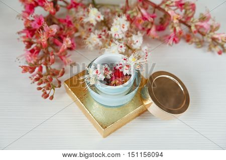 There White and Pink  Branches of Chestnut Tree,Goden Present Box with Bottle Cream are on White Table