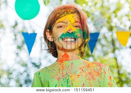 Portrait of smiling ten years old boy with face smeared with colored powder on Holi color festival