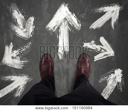 Businessman chooses which directional white arrow follow