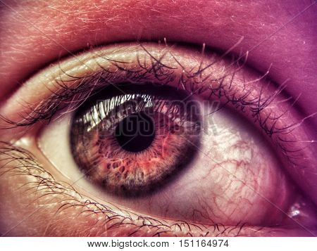 Close up photo of man eye.In eye you can see a houses in front of eye.
