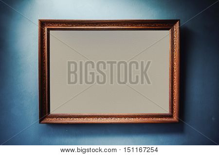 Empty wooden frame on pale blue wall with decorative carvings.