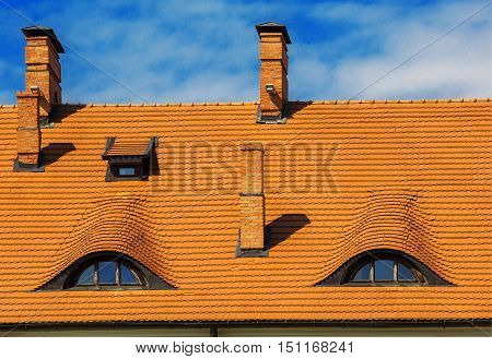 dormer windows of the old house with a tiled roof