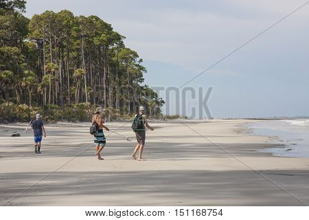 Three teenage male tourists strolling on a beach in South Carolina