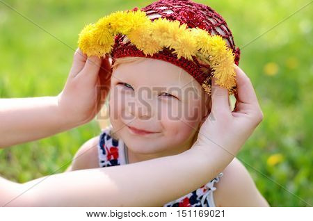 child on a walk in a chaplet from dandelions