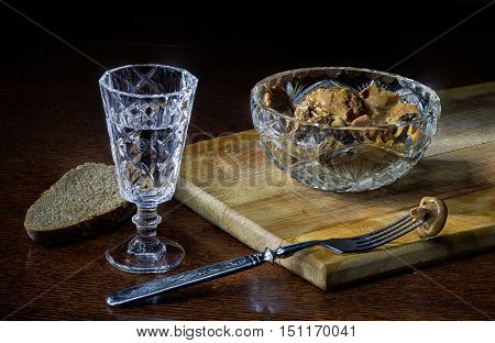 Vodka in glass and salted mushrooms and black bread