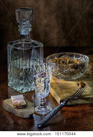 Vodka in glass and decanter and salted mushrooms