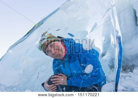 Cheerful Girl Looking Through The Transparent Ice Floe In Lake Baikal