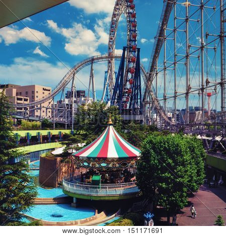 Tokyo - May 2016: Carousel, ferris wheel and rollercoaster at Tokyo Dome amusement park. Elevated view, retro look.