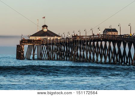 Fishermen on the Imperial Beach fishing pier at dawn in San Diego, California.