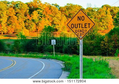 No outlet sign with dead end written in with colorful foliage in background.