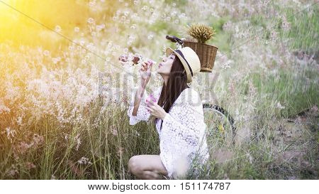 Woman blowing bubbles in meadow warm light. travel and sunset, soft and select focus