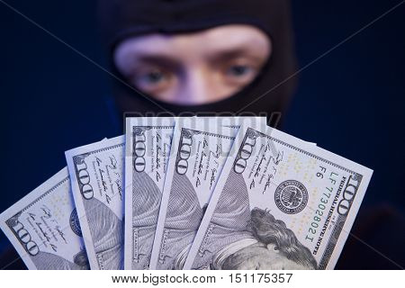 Robber holding money isolated on dark blue background