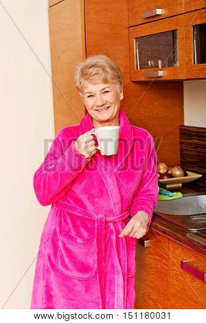 Happy senior woman standing in kitchen and drinking coffee or tea