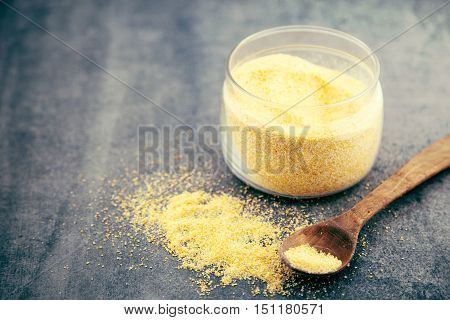 Yellow Corn Flour In A Glass Jar On A Rustic Table. Ingredients For Preparation Of A Italian Traditi