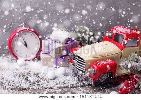 Christmas background. Vintage decorative car clock wrapped gifts berries and branches fur tree on aged wooden background. Selective focus. Drawn snow.