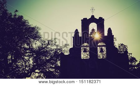 Spanish Mission Espada church bells in silhouette as the sun sets behind mission in San Antonio Texas