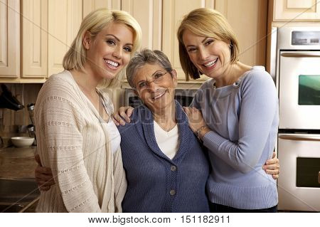 Three generations of beautiful women smiling in the kitchen.